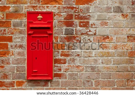 traditional british postal box against a red brick wall