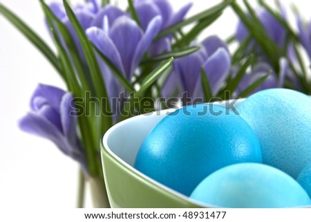traditional easter eggs in cup and crocuses behind