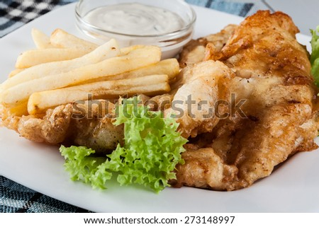 Traditional fish and chips with tartar sauce on a plate