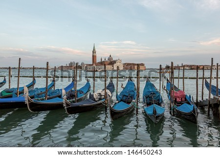 Traditional gondolas with the bell tower of the Saint Giorgio Maggiore Church on background (view from San Marco embankment) - Venice, Italy