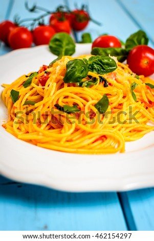 Traditional italian cuisine spaghetti with tomato sauce, basil and cheese on blue table