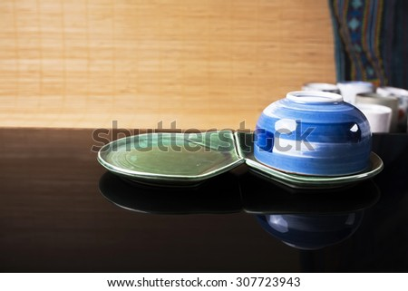 Traditional Japanese pottery with reflection on the black glass