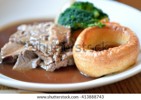 Traditional Sunday roast beef dinner with Yorkshire puddings and gravy