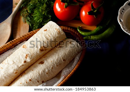 Traditional Turkish wrap (pita) bread on a dark table setting.