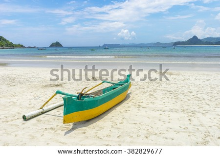 Traditional wooden boat park at sea shore with cloudy skies at South Lombok island, Indonesia