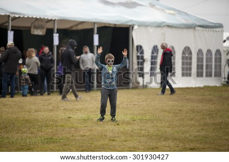 Traena, Norway - July 10 2015: little boy with make up on his face having fun playing football on the festival field Traenafestival, music festival taking place on the small island of Traena