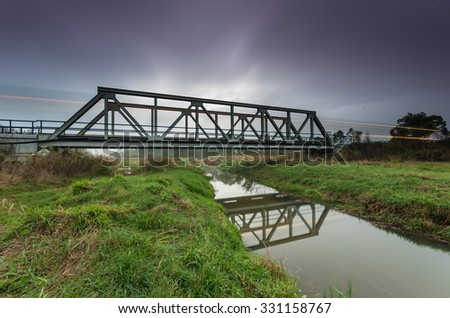 Train lights on railway steel truss bridge in Poland, over small river
