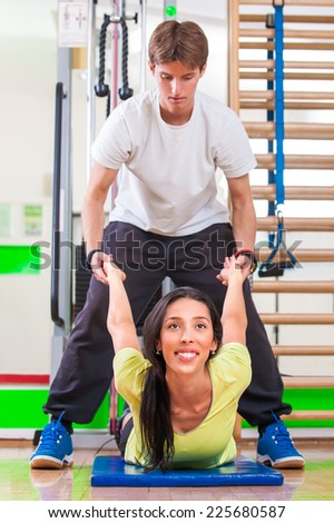 Training instructor. Woman with personal trainer in gym