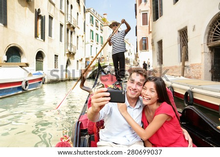 Travel couple taking selfie picture in gondola on Venice vacation. Beautiful lovers on a romantic boat ride across the Venetian canals taking self-portrait pictures with smartphone during holiday.