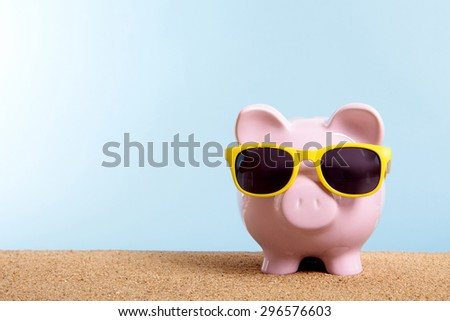 Travel money concept, summer vacation savings, piggy bank sunglasses.  Copy space.