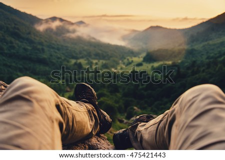 Traveler young man enjoying view of nature at sunset, point of view shot