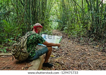 Travelling man sitting and looking at the map in the bamboo forest
