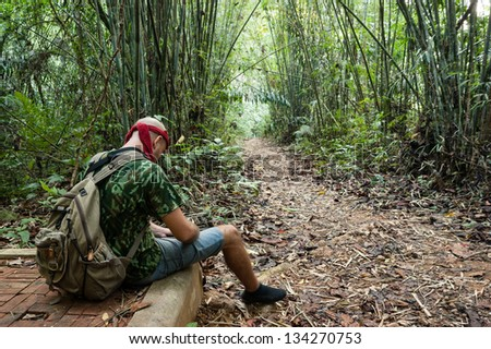 Travelling man sitting in the bamboo forest
