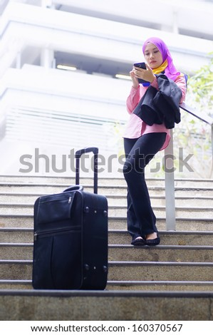 Travelling young businesswoman using tablet phone outdoor