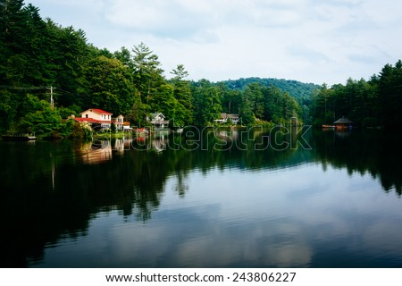Trees and houses reflecting in Lake Sequoyah, Highlands, North Carolina.