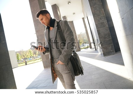 Trendy businessman walking by modern building