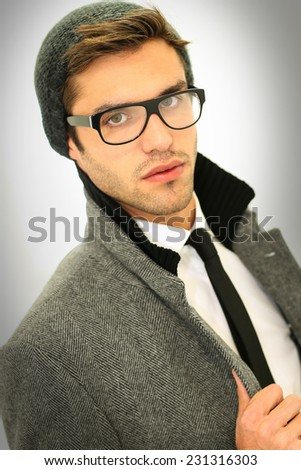 trendy mens glasses 9sie  Trendy guy with winter coat, hat and eyeglasses, isolated
