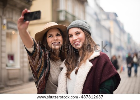 Trendy young women taking selfies in the city