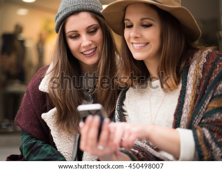 Trendy young women using smartphone in the city