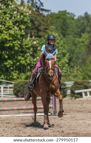 "TRESTINA, CZECH REPUBLIC - MAY 16: Young horsewoman on the brown horse at ""Equestrian Hobby Series 2015"" on May 16, 2015  in Trestina, Czech Republic."