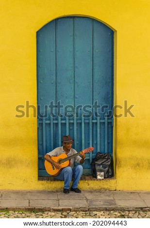 TRINIDAD, CUBA - DECEMBER 7, 2013: Man playing the guitar in front of one of the colonial buildings. Cuban music is an attraction for the over 2 million tourists who go to Cuba each year.
