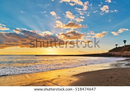 Tropical beach at beautiful sunset.Costa Adeje, Tenerife, Spain