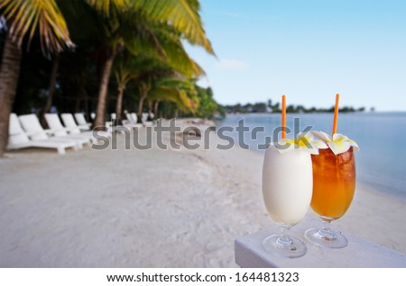 Tropical cocktails served outdoor on Pacific Island resort with beach chairs, palm trees sandy beach and turquoise water in the background.Concept photo of couples travel and tourism