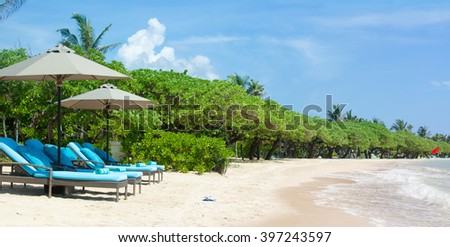 tropical empty beach view with sun loungers and waves