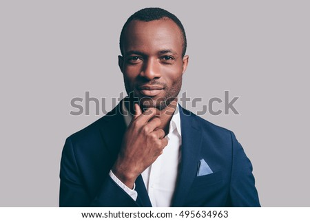 True elegance. Portrait of thoughtful young African man in smart casual jacket holding hand on chin and looking at camera while standing against grey background