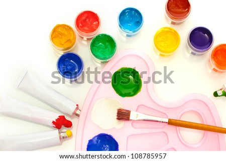Tubes with colorful watercolors and jars with gouache and palette on white background close-up