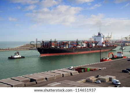 Tugs and container ship leaving port