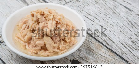 Tuna fish flakes in white bowl over wooden background