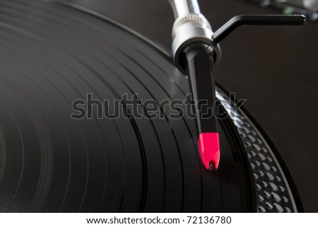 Turntable playing vinyl record with music. Overhead shot of turntables needle scratching records. Focus on head shell. DJ audio equipment for studio, party or concert. Close up, macro