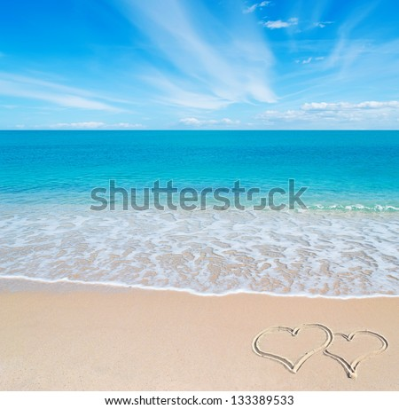 turquoise water and golden sand in Sardinia with two hearts drawn in the sand on a cloudy day