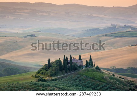 Tuscany, Italy. Lonely farmhouse with green and golden meadow hills, olive trees. Beautiful country landscape.