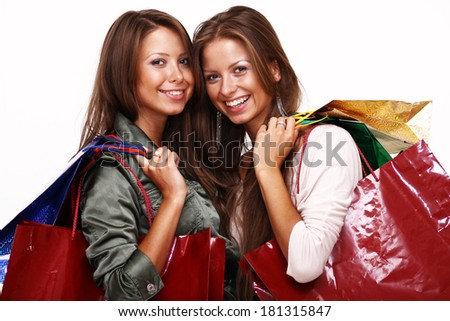 Twins sisters holding shopping bags on white isolated