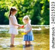 Two adorable little sisters playing with paper boats by a river on warm and sunny summer day - stock photo