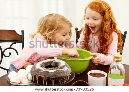 Two adorable preschool sisters mixing batter at kitchen table.