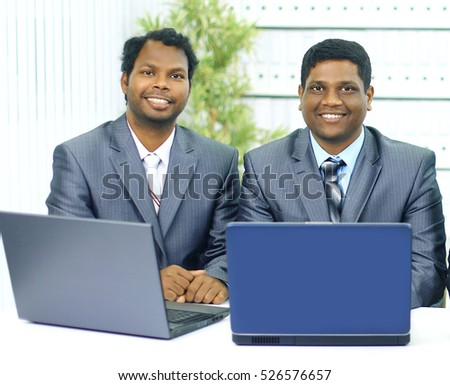 Two african-american in the office work of the laptop.