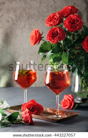 Two alcohol cocktails set with red roses. Romantic evening, valentine day celebration, chillout and party concept