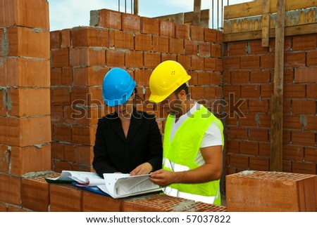 Two architects having a discussion and reading folders or looking on projects in a house under construction outdoor