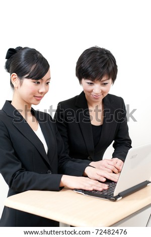two asian business woman working with laptop