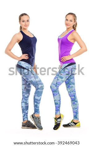 Two athletic girls in sportswear perform various fitness exercises. Active lifestyle, healthcare. Twin sisters. Isolated over white.