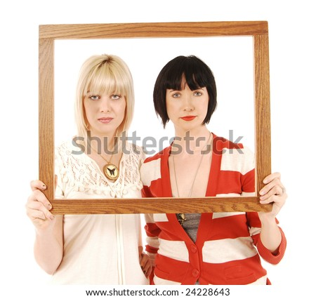 Two attractive women framing their faces with a picture frame.