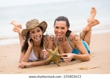 two beautiful girl friends lying down at the beach with a starfish