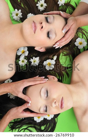 Two Beautiful girl with flower in spa  having massage