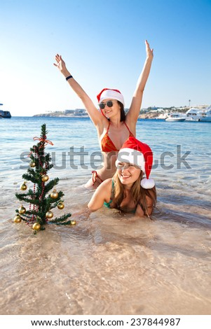 Two beautiful girls in bikinis in Christmas red hat with a Christmas tree lying on the beach summer day