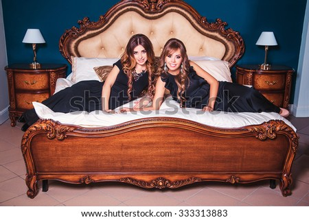 Two beautiful girls on a bed
