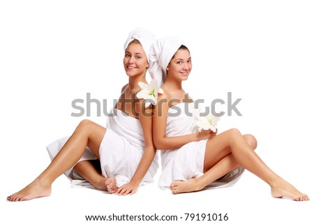 Two beautiful girls with towels and flowers relaxing in spa