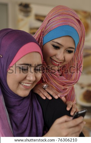 Two beautiful Muslim girls are using the phone with a cheerful face